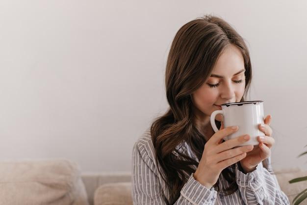 Femme aux cheveux longs en pyjama bleu appréciant l'arôme du thé