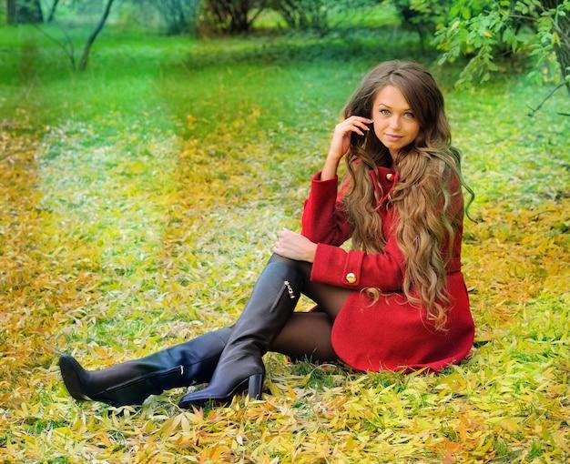 Femme aux cheveux longs reste dans le parc en automne.