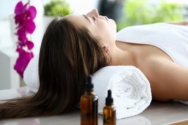 Femme aux cheveux longs s'allongeait sur le dos sur une table de massage avec les yeux fermés.