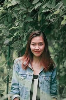 Une femme aux cheveux longs se tenant sous un arbre