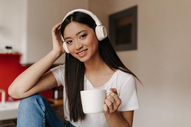 Femme aux cheveux longs en t-shirt blanc se pencha et regarde devant