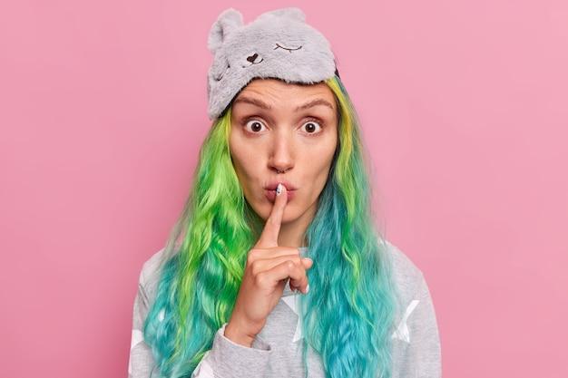 Une femme aux cheveux longs teints fait un geste de silence ou de tabou raconte des informations secrètes porte un masque de sommeil et des poses de pyjama sur rose