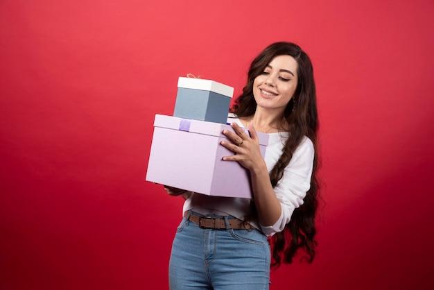 Femme aux cheveux longs tenant des boîtes présentes sur fond rouge. photo de haute qualité