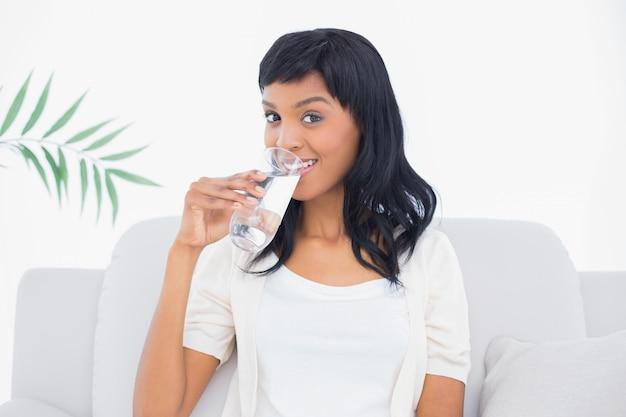 Femme aux cheveux noirs amusée portant des vêtements blancs et dégustant un verre d'eau