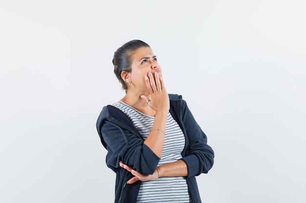 Femme aux cheveux noirs appelant quelqu'un avec une voix forte en chemise