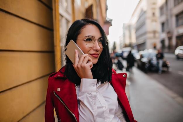 Femme aux cheveux noirs en chemise blanche et veste rouge parlant au téléphone sur le mur de la ville