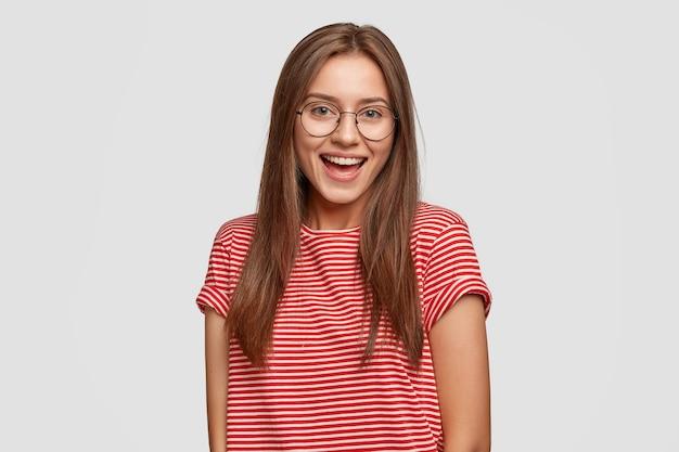 Femme aux cheveux noirs joyeuse avec un sourire agréable à pleines dents, porte des lunettes rondes transparentes, un t-shirt rayé