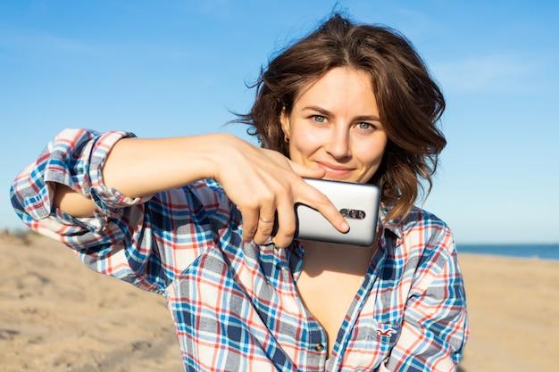 Une femme aux cheveux noirs joyeuse sourit, prend des photos au téléphone, se promène le long de la plage, profite du soleil éclatant un jour d'été. concept de vacances d'été en mer et style de vie
