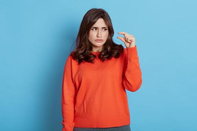 Femme aux cheveux noirs portant un pull orange montrant un geste de petite taille avec un doigt isolé sur un mur bleu