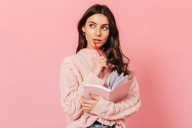Femme aux cheveux noirs en pull tricoté lève les yeux pensivement. lady pense quoi écrire dans un nouveau livre.