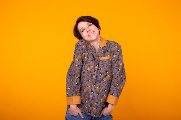 Femme aux cheveux noirs en pyjama à la maison souriant largement sur jaune