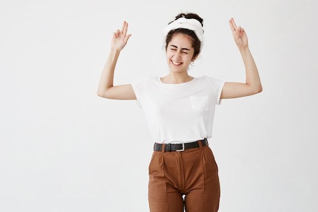 Une femme aux cheveux noirs, ravie et excitée, pointe vers l'espace de copie, ferme les yeux, sourit largement, fait de la publicité. heureuse femme en t-shirt blanc pose contre un mur blanc avec une zone de copie pour le texte promotionnel