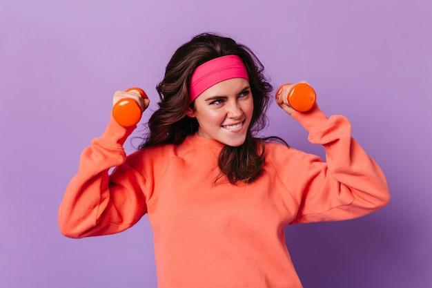 Femme aux cheveux noirs sourit et fait des exercices avec des haltères