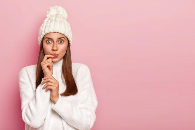 Une femme aux cheveux noirs surprise a l'air étonnamment, garde les lèvres arrondies, porte un chapeau d'hiver et un pull blanc neige, vêtue d'une tenue chaude pose contre le mur rose
