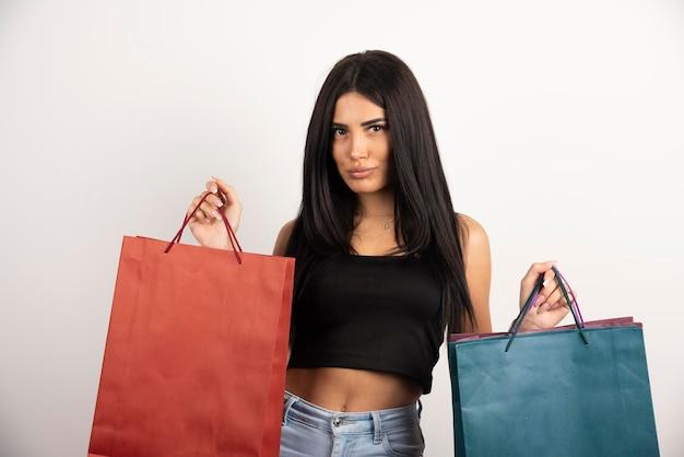 Femme aux cheveux noirs tenant un tas de sacs à provisions. photo de haute qualité