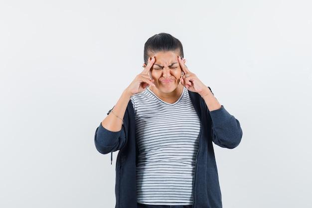 Femme aux cheveux noirs touchant ses tempes en chemise