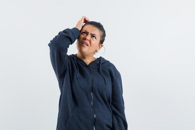 Femme aux cheveux noirs en veste se gratter les cheveux et à la confusion