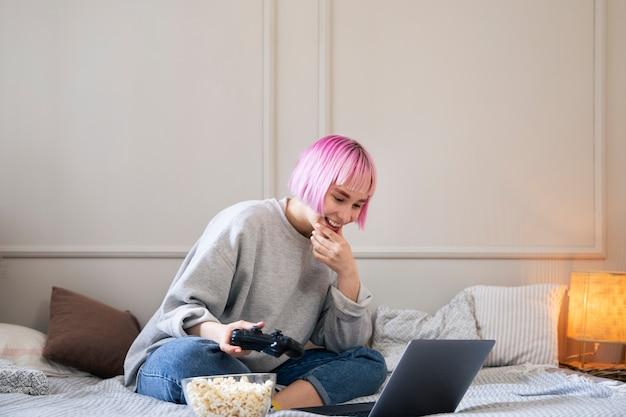 Femme aux cheveux roses jouant avec un joystick sur l'ordinateur portable