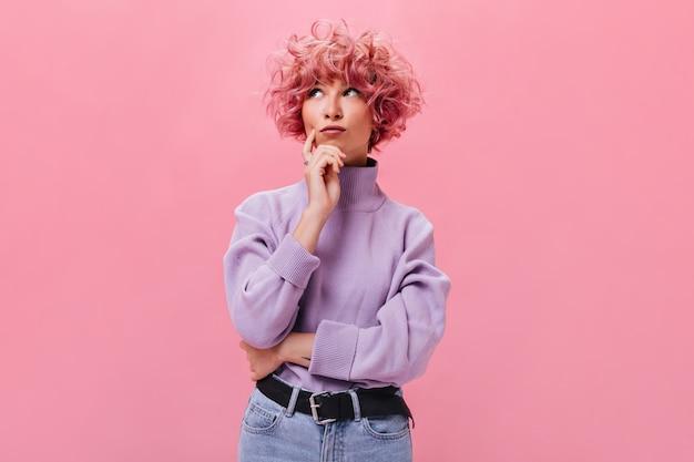 Une femme aux cheveux roses regarde pensivement sur un mur isolé