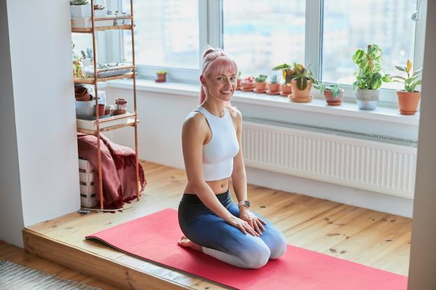 Une femme aux cheveux roses en survêtement est assise sur les genoux à l'entraînement à domicile