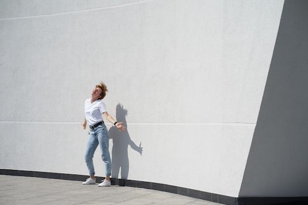 Femme aux cheveux rouges courts dansant devant un mur blanc extérieur