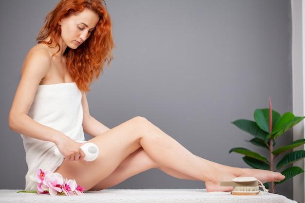 Femme aux cheveux rouges faisant un massage lpg à la maison en appartement
