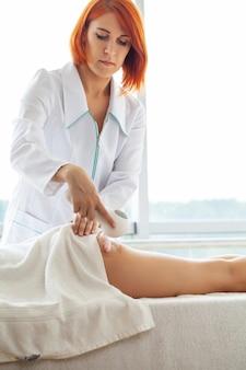 Femme aux cheveux rouges faisant un massage lpg à la maison dans un appartement avec fenêtres panoramiques