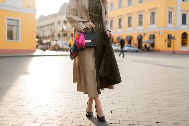Femme aux cheveux rouges et maquillage lumineux marchant dans la rue. portant un manteau beige et une robe verte.