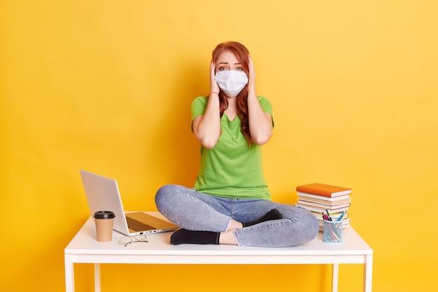 Femme aux cheveux rouges portant un masque médical et regarde directement la caméra, étant sous le choc, jeune fille habillée en t-shirt et jeans, assise sur la table, isolée sur fond jaune.