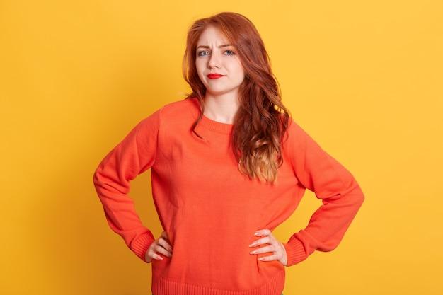 Femme aux cheveux rouges portant un pull orange avec une expression faciale perplexe