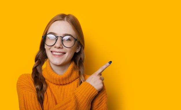 Femme aux cheveux rouges avec des taches de rousseur et des lunettes pointe vers l'espace vide jaune près d'elle