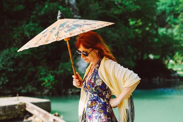 Une femme aux cheveux rouges tient un parapluie