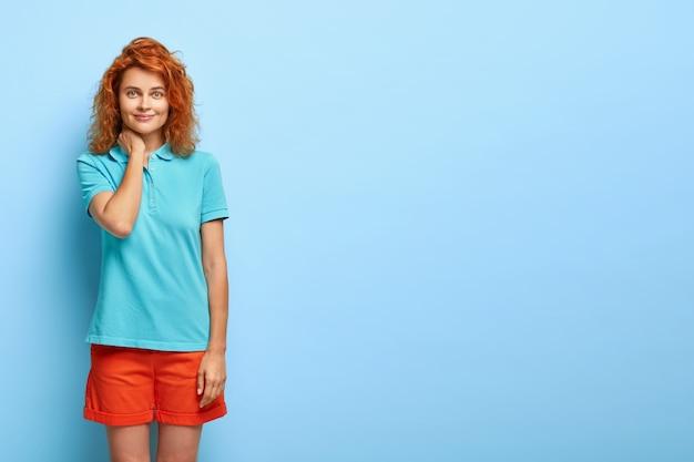 Femme aux cheveux rouges timide et polie avec un sourire tendre, touche le cou et agit comme un ange, reçoit les éloges des parents pour une bonne étude