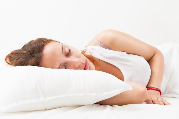 Femme aux cheveux roux dormie sur un coussin blanc au lit à la maison