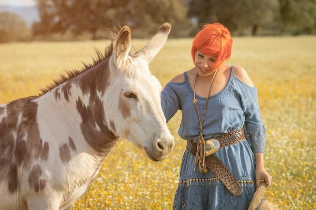 Femme aux cheveux roux près d'un âne