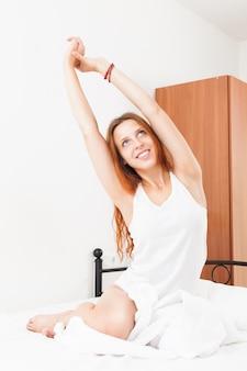 Femme aux cheveux roux s'étendant sur un coussin blanc au lit à la maison