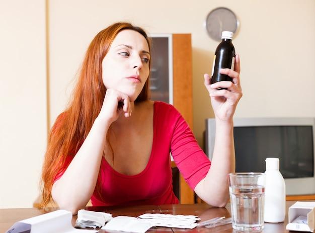 La femme aux cheveux roux se penche sur les médicaments dans le manuel à la maison