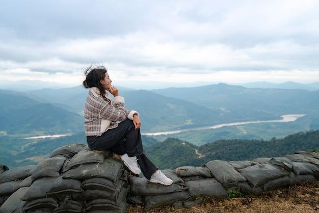 Femme aux cheveux venteux s'asseoir et penser à regarder la vue sur la rivière khong et la montagne dans le brouillard avec le ciel de nuages