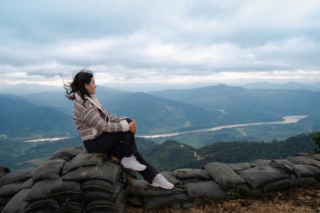 Une femme aux cheveux venteux s'assoit et regarde la vue sur la rivière khong et la montagne dans le brouillard au point de vue de pha tang