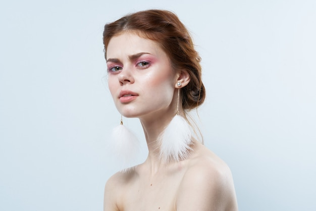 Femme aux épaules nues bijoux fraîcheur maquillage lumineux recadrée vue isolée.
