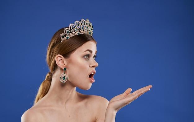 Une femme aux épaules nues et un diadème sur sa tête fait des gestes