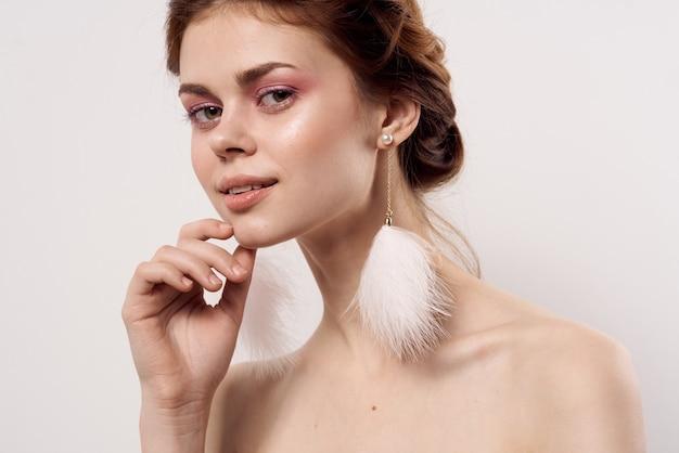 Femme aux épaules nues maquillage lumineux boucles d'oreilles moelleuses mode fond clair