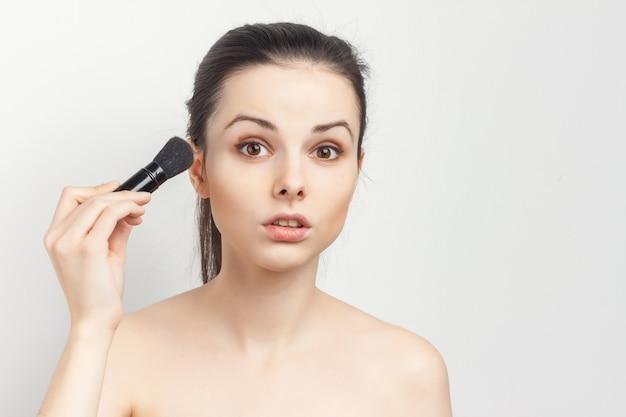 Femme aux épaules nues avec un pinceau dans ses mains en appliquant le maquillage.