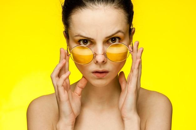 Femme aux épaules nues portant des lunettes de cheveux rassemblés sourire. photo de haute qualité