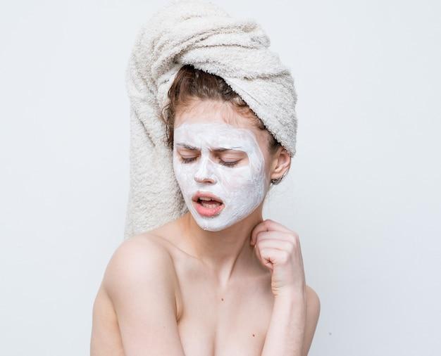 Femme aux épaules nues avec une serviette sur sa tête masque de soins de la peau