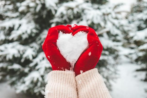 Femme aux gants rouges tient la neige dans les mains en forme de coeur.