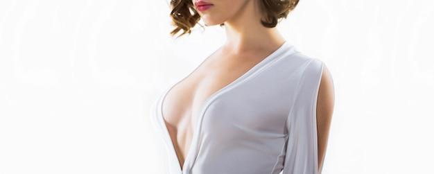 Femme aux gros seins. poitrine féminine sensuelle. implants en silicone. seins nus érotiques, seins. femme sexy en robe blanche érotique