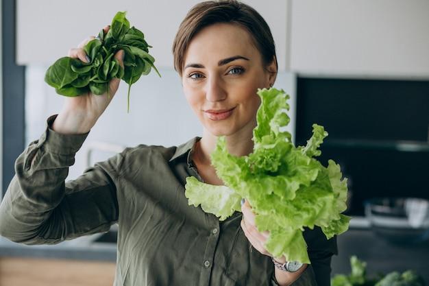 Femme aux légumes verts dans la cuisine