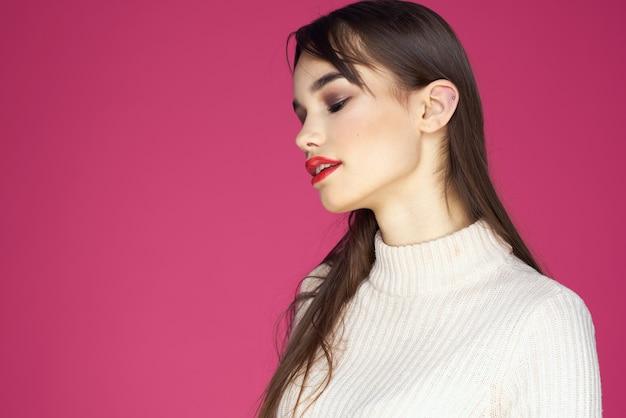 Femme aux lèvres rouges maquillage lumineux chemisier blanc cheveux longs fond rose