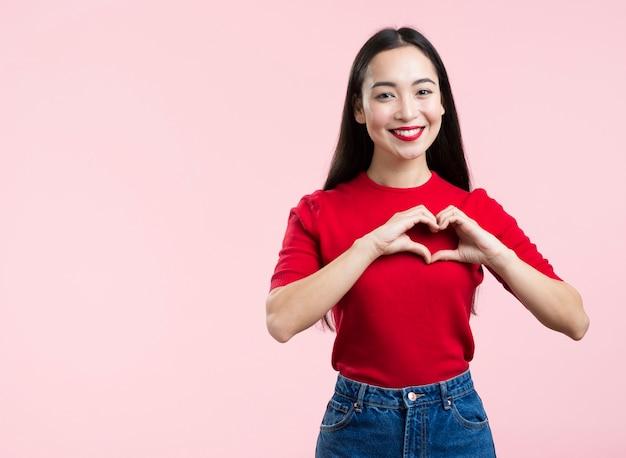 Femme aux lèvres rouges montrant le signe du cœur